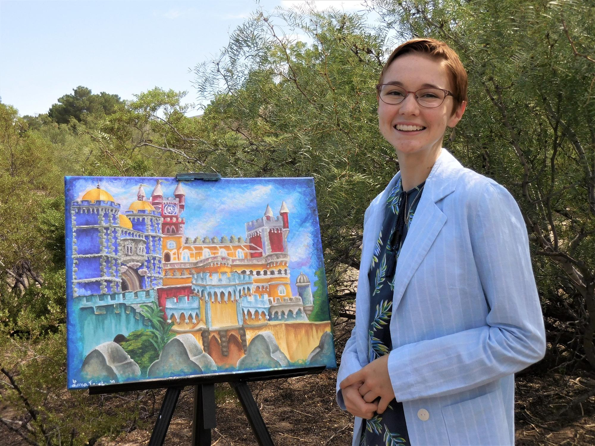 Lara in her home in Las Cruces, New Mexico, with an original painting of Pena Palace