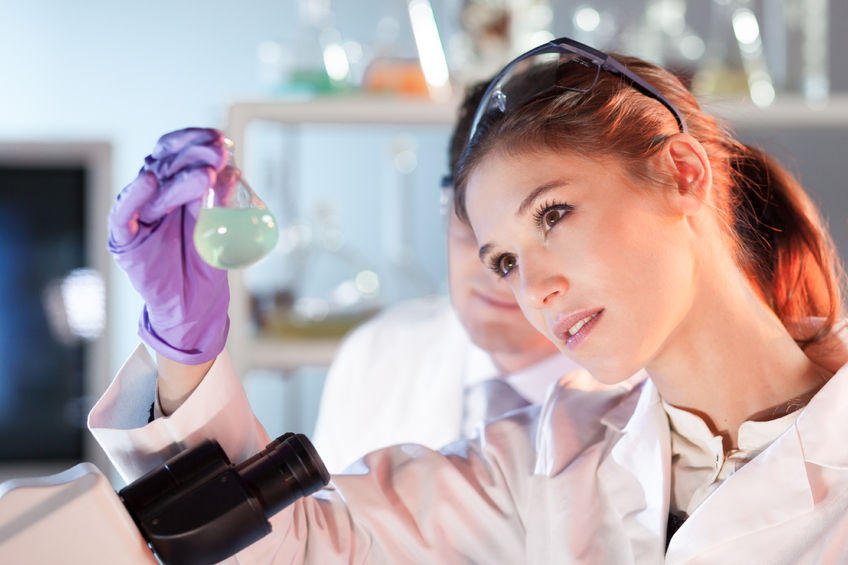 Woman in Science Lab Coat Conducting an Experiment