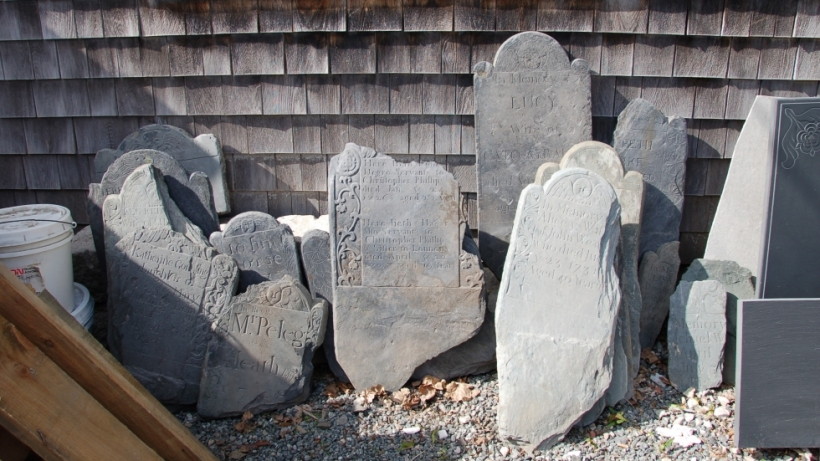 A dozen slate gravestones (18th century) lean against a shingled shed. Many are cracked or broken.