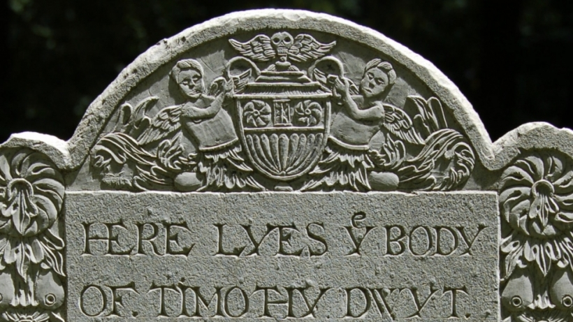 A 17th-century gravestone decorated with deeply carved borders and tympanum.